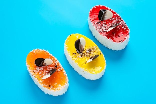 Drei mehrfarbige kuchen auf hellblauem hintergrund. ungesundes essen