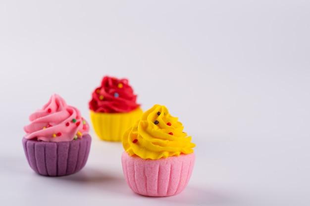 Drei mehrfarbige miniaturzucker-cupcakes auf hellem hintergrund