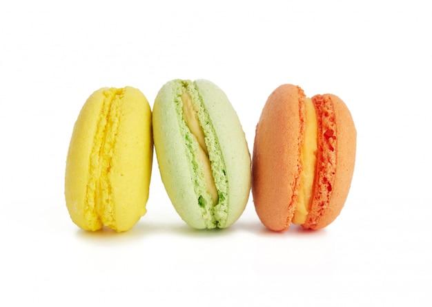 Drei mehrfarbige runde gebackene macarons-kuchen, isoliert auf einem weiß