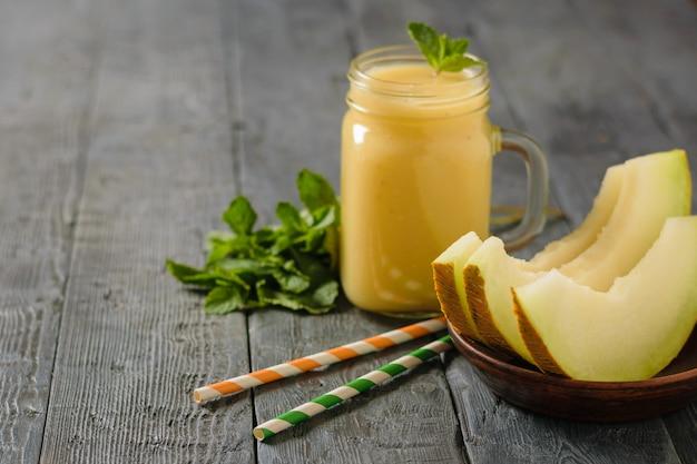 Drei melonenscheiben, cocktailstrohhalme und smoothies auf einem holztisch