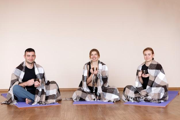 Drei menschen in plaids sitzen nach dem yoga