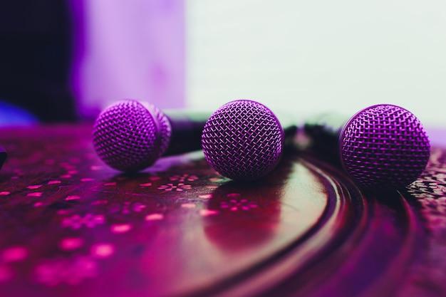 Drei mikrofone in der gruppe auf roter tabelle mit kopienraum.