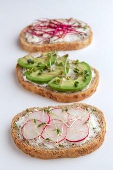 Drei mikrogrüne sandwiches auf weißer oberfläche