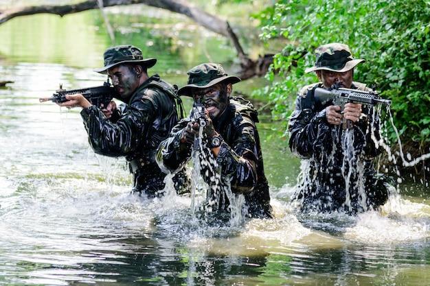 Drei militäroffiziere erhoben sich aus dem wasser, um den feind anzugreifen