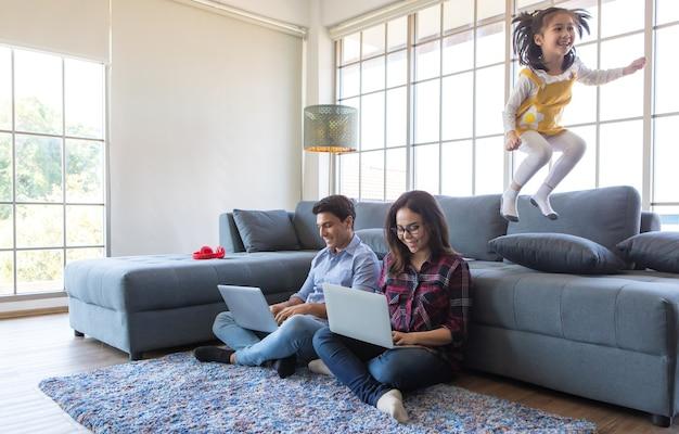 Drei mitglieder einer vielfältigen familie, ein kaukasischer vater, eine asiatische mutter und eine kleine halbtochter verbringen zeit zusammen im wohnzimmer des hauses. mädchen springt auf sofa, während mama und papa zu hause arbeiten und sich aufmuntern.