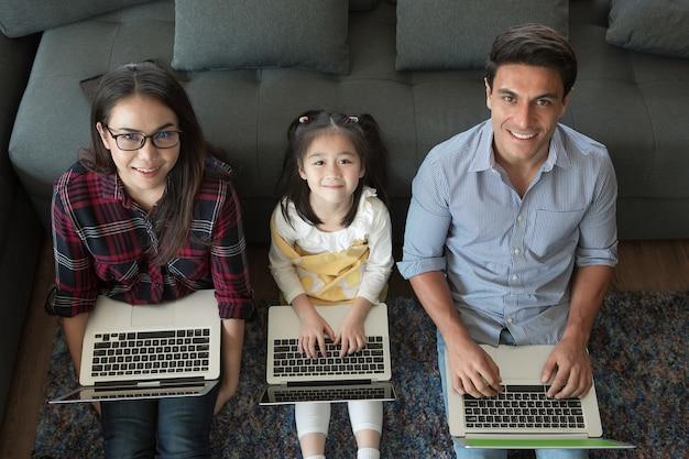 Drei mitglieder einer vielfältigen familie, ein kaukasischer vater und eine asiatische mutter und eine kleine halbe tochter, die zusammen im wohnzimmer des hauses sitzen und 3 laptop-notebook-computer verwenden. idee für die arbeit zu hause.