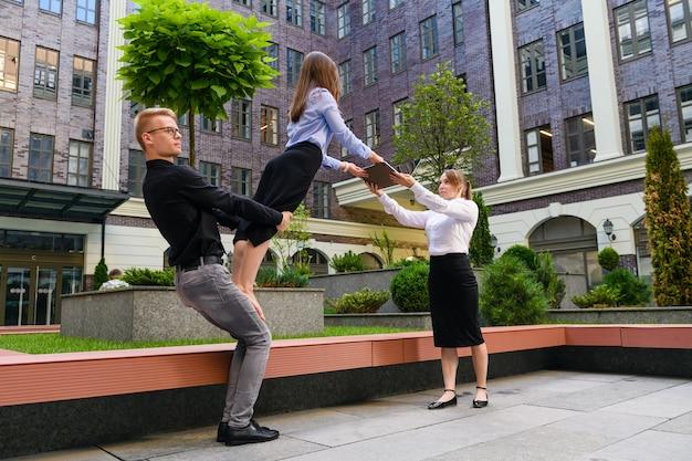 Drei mitglieder in balance asana von acro yoga mit basispartner, flyer und spotter mit laptop, teamwork, geschäfts- und sportkonzept