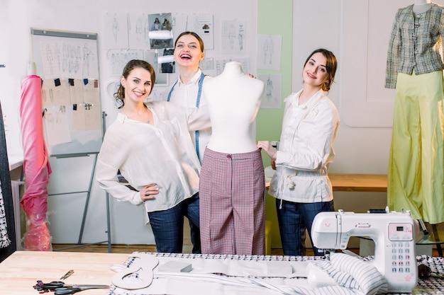 Drei modedesigner oder schneider, die in die kamera lächeln und handgefertigte hosen auf einer schaufensterpuppe im gemütlichen atelierstudio messen. schneiderin, schneiderin, mode- und showroom-konzept