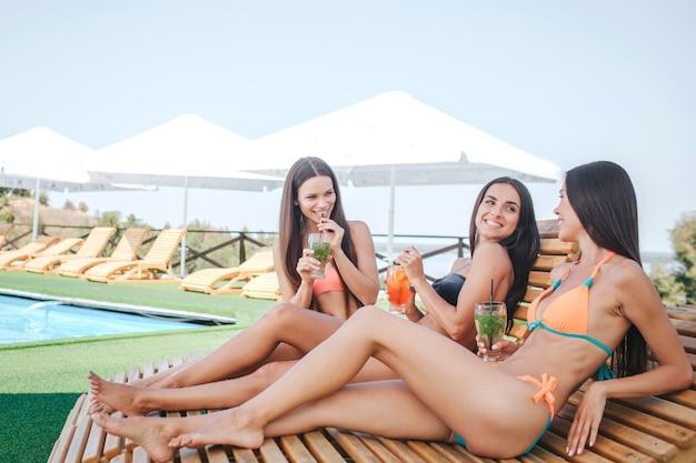 Drei modelle sitzen und liegen auf sonnenliegen. sie chillen. junge frauen trinken cocktails und ruhen sich aus. models schauen sich an. sie verbringen zeit miteinander.