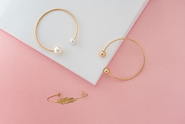 Drei moderne goldene armbänder auf rosa und weißer anzeige