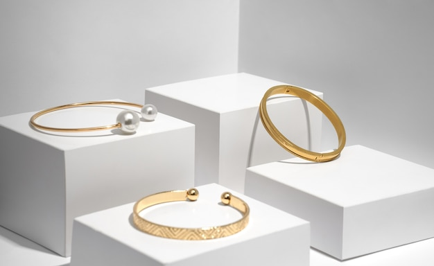 Drei moderne goldene armbänder auf weißen geometrischen kästen