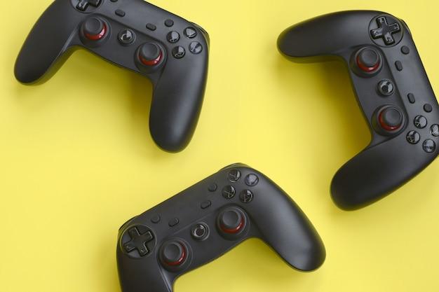 Drei moderne schwarze gamepads auf gelbem hintergrund. lass uns zusammen mit dem konzept der freunde videospiele spielen. kooperatives teamplay