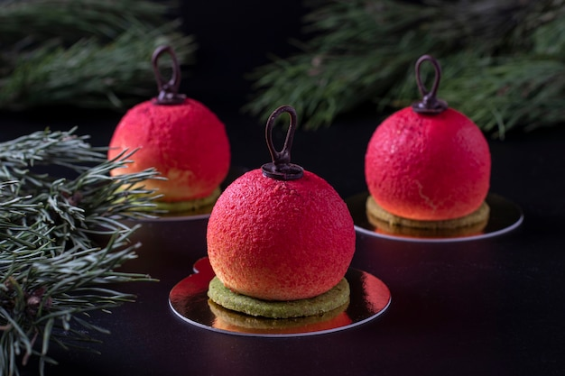 Drei mousse-desserts in form von weihnachtskugeln auf dunklem hintergrund. neujahrsparty. horizontalformat