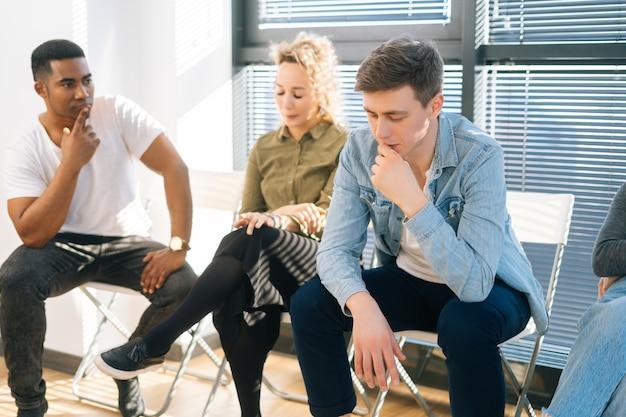 Drei müde bewerber, die vorbereitungen für ein vorstellungsgespräch treffen, das ergebnis des vorsprechens erwartet, sich besorgt und gestresst fühlt, in der warteschlange in der modernen bürolobby sitzt.