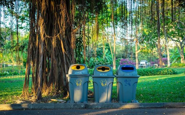 Drei mülleimer in einem park mit park des grünen baum- und betriebshintergrundes öffentlich