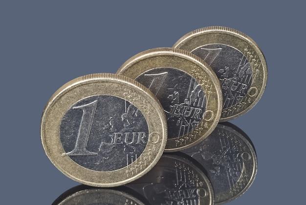 Drei münzen von einem euro auf dem dunklen spiegelnden hintergrund