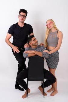 Drei multiethnische freunde zusammen gegen weiße wand