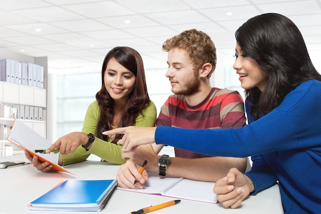 Drei multikulturelle studenten, die zusammen studieren