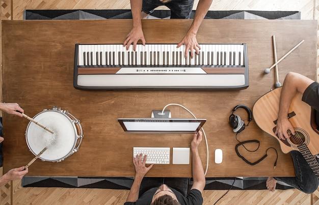 Drei musiker arbeiten daran, musik zu machen. komposition von musikinstrumenten auf einem holztisch. musikaufnahmevorgang.