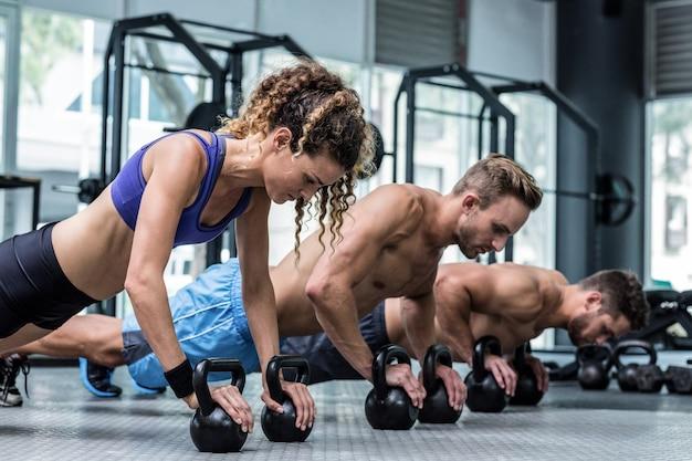 Drei muskulöse athleten auf einer plankenposition