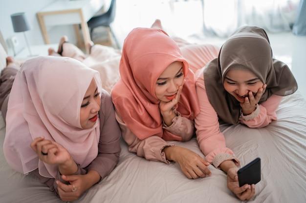 Drei muslimische frau liegen und genießen mit smartphone auf dem bett