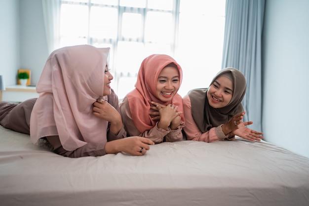 Drei muslimische frau lügen und plaudern gerne auf dem bett