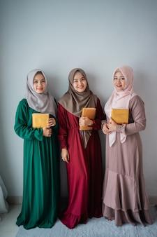 Drei muslimische frauen, die lächeln, halten das heilige buch al-quran