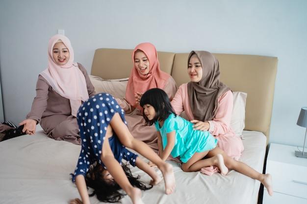 Drei muslimische frauen genießen es, mit ihrer tochter im schlafzimmer zu spielen