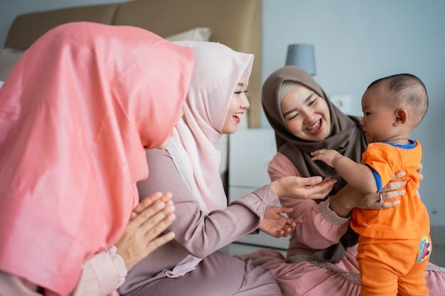 Drei muslimische frauen spielen gerne mit einem kleinen jungen, wenn sie auf dem boden sitzen
