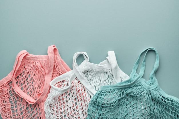 Drei netzbeutel in verschiedenen farben. draufsicht. null abfall lebensmitteleinkaufskonzept.