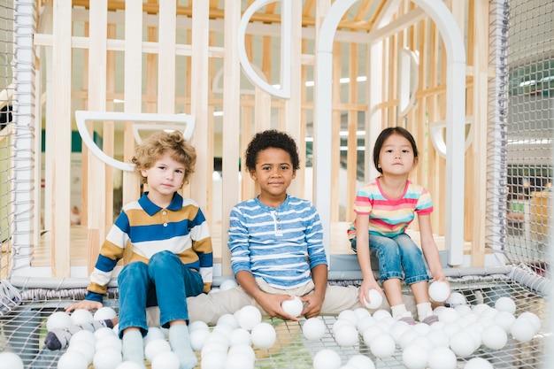 Drei niedliche kinder verschiedener ethnien, die mit weißen luftballons auf spielplatz im freizeitzentrum spielen