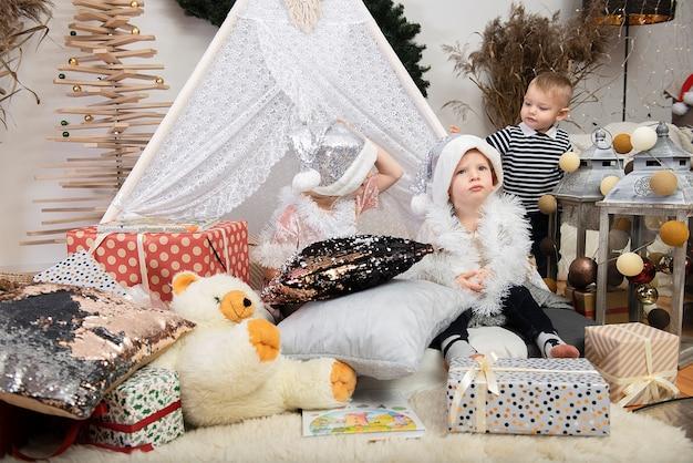 Drei niedliche kinderkinder, die weihnachtsmützen tragen, die zwischen geschenkboxen in einem geschmückten haus spielen. frohe weihnachten und frohe feiertage!
