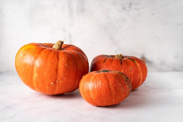 Drei orangefarbene kürbisse unterschiedlicher größe auf weißer oberfläche. herbstkonzept