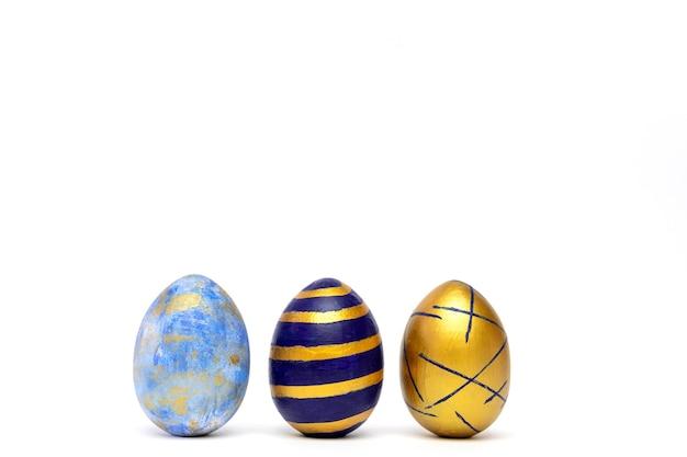 Drei ostereier, blau, weiß und golden auf weißem tisch gefärbt