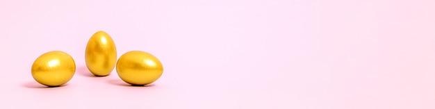 Drei ostereier verziert mit goldfarbe auf einem rosa hintergrund. konzept für ostern, frühling. selektiver fokus. speicherplatz kopieren.