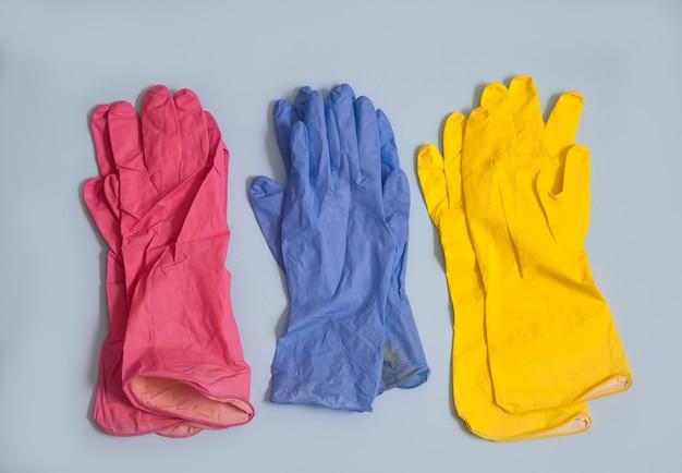 Drei paar mehrfarbige gummihandschuhe liegen auf blau