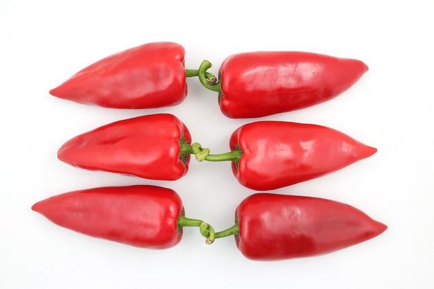 Drei paar rote paprika auf weiß