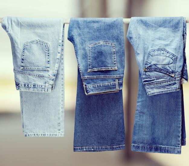 Drei paar verschiedene jeans, die an der schiene hängen