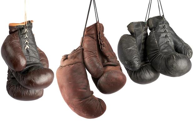 Drei paare der sehr alten ledernen boxhandschuhe der weinlese, die an den spitzeen hängen
