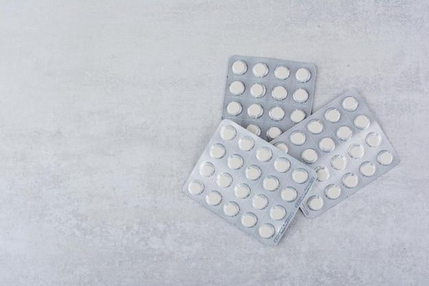 Drei packungen medikamente auf marmoroberfläche. foto in hoher qualität