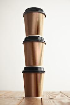 Drei papierhandwerksbecher mit schwarzen kappen, die in der säule auf rustikalem weinlesetisch stehen, lokalisiert auf weiß