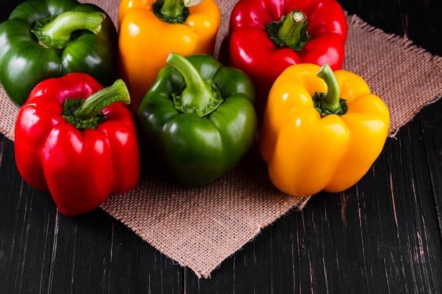 Drei paprika auf einem holztisch, gemüsesalat kochen