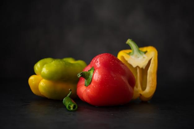 Drei paprika auf schwarzem grund