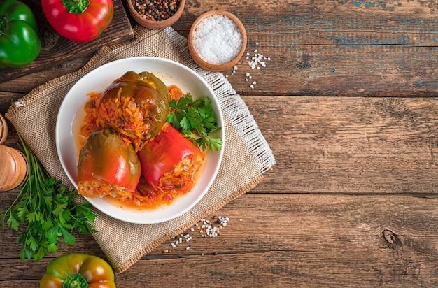 Drei paprika gefüllt mit fleischreis und gemüse in einem weißen teller auf holzuntergrund