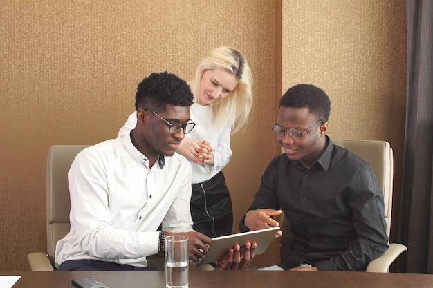 Drei personen, die touchscreen-computer während der arbeit betrachten