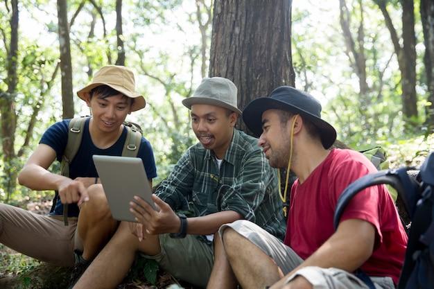 Drei personen, die zusammen einen tablet-pc verwenden