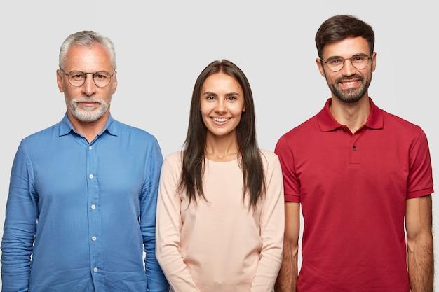 Drei personen im schuss. ernsthafter älterer männlicher rentner, gekleidet in formelles hemd