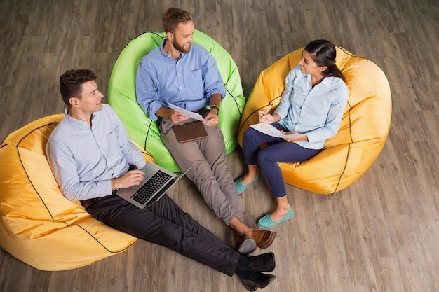 Drei personen sitzen auf sitzsack stühle und arbeits