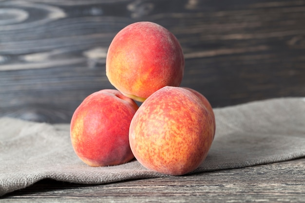 Drei pfirsiche auf einem holztisch mit einer leinenserviette