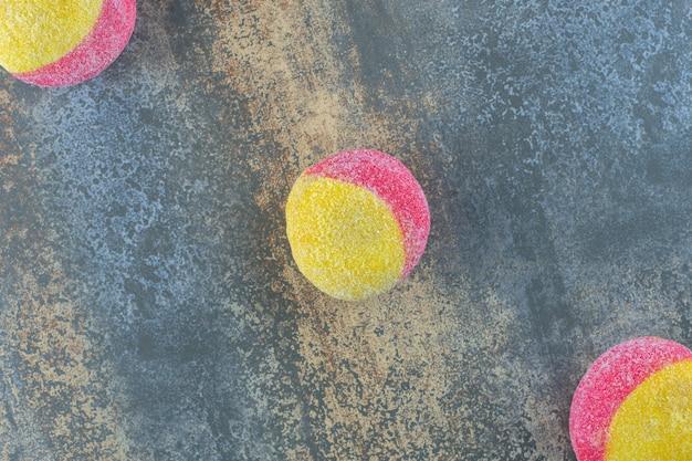 Drei pfirsichförmige kekse auf dem marmorhintergrund.